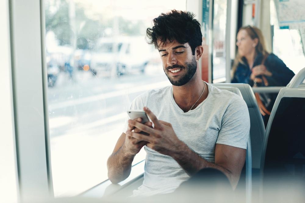 Junger Mann schaut auf sein Smartphone