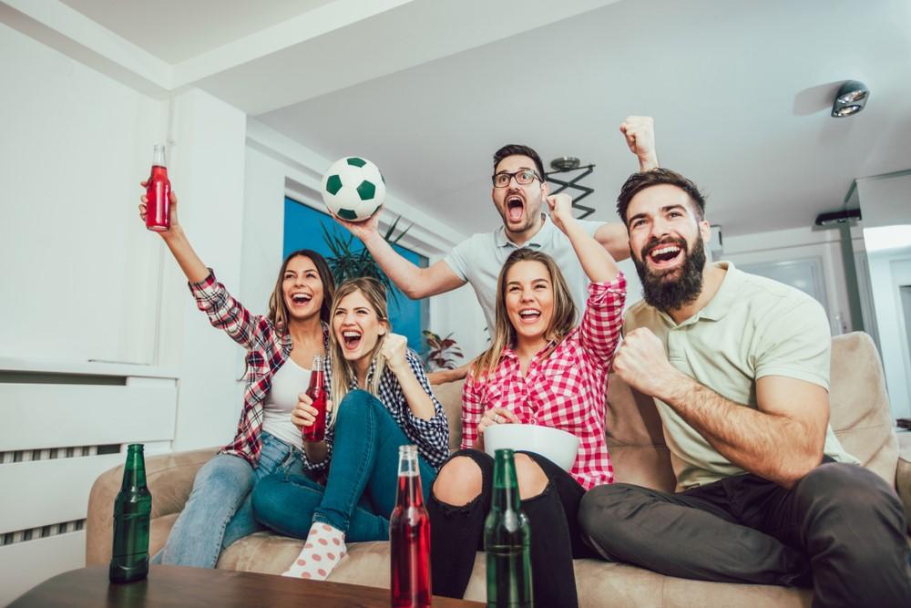 Fußballfans sitzen auf einem Sofa und verfolgen ein Fußballspiel