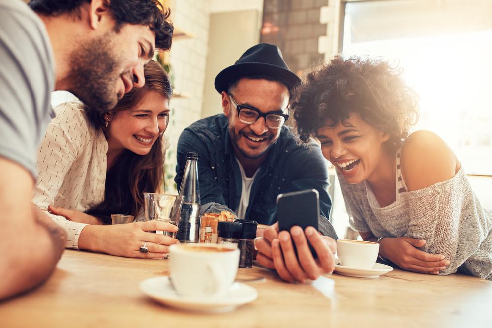 Freunde sitzen vor einem Smartphone