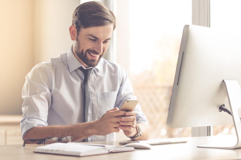 Junger Mann sitzt mit Smartphone am Schreibtisch